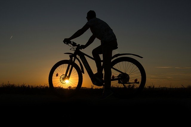 man riding an ebike at sunset