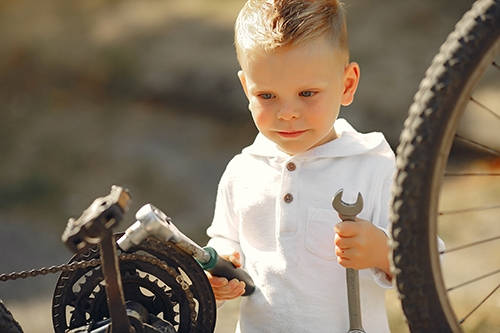 Little boy fixing his bike in a park